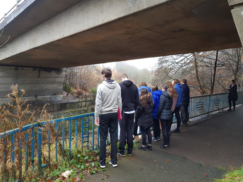 Students stand under a large concrete bridge