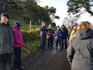 The walking group gather around a man on a road to listen to him talk about hedges