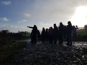 Participants stand in a group on the muddy ground